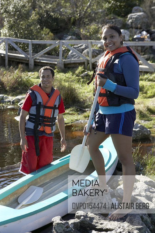 Portrait of mixed race man and woman with canoe.