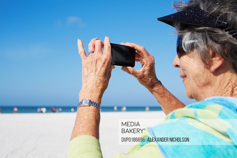 Senior using phone to take digital photo on beach