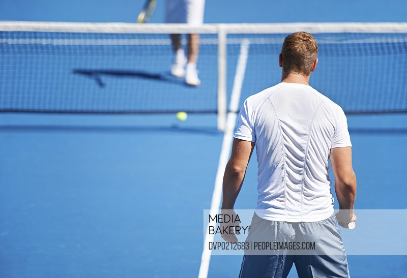 Shot of two people playing tennis outside