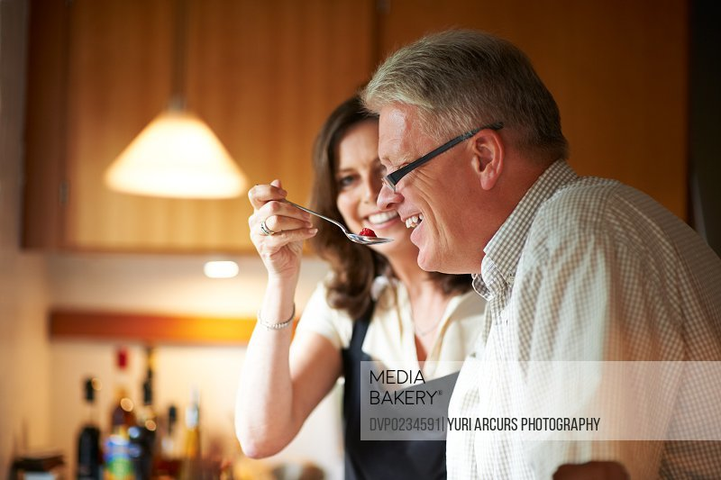 Middle-aged wife playfully feeding her husband with a spoon