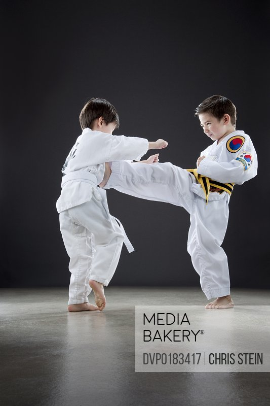 Two Young Half Asian brothers 4 and 7 years old in a white karate uniforms and fighting and kicking each other