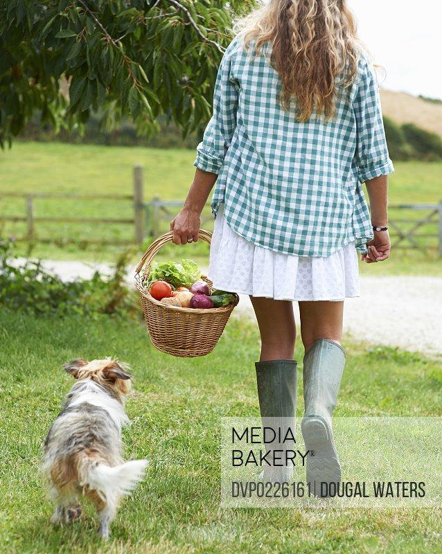 Woman in farmyard carrying basket of vegetables
