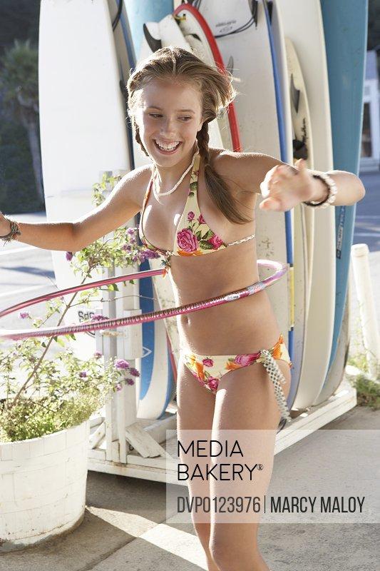 Girl (13-14) in bikini spinning plastic hoop