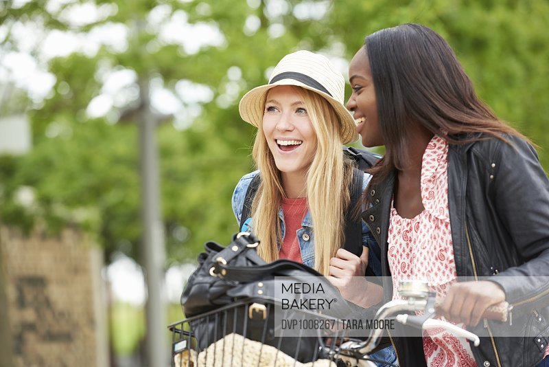 Young women riding bikes in city park laughing