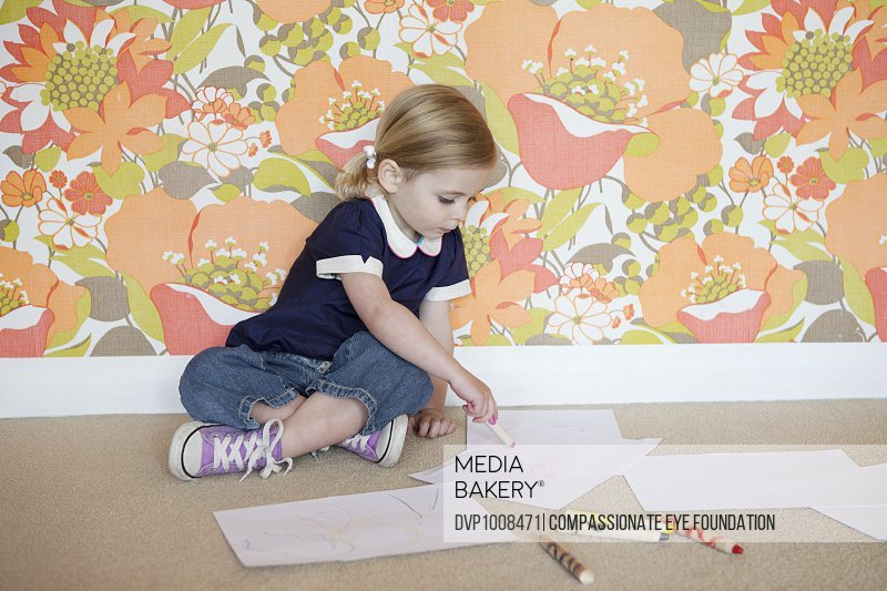Girl colouring on floor in living room