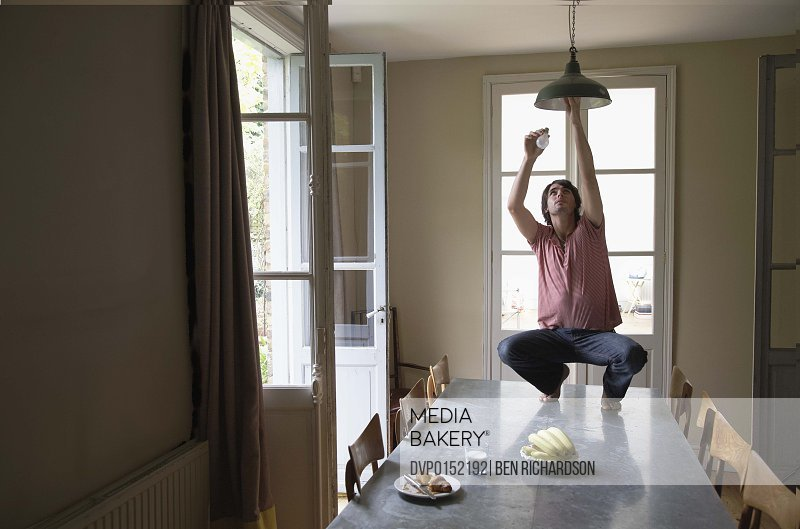 Man on table changing a light bulb