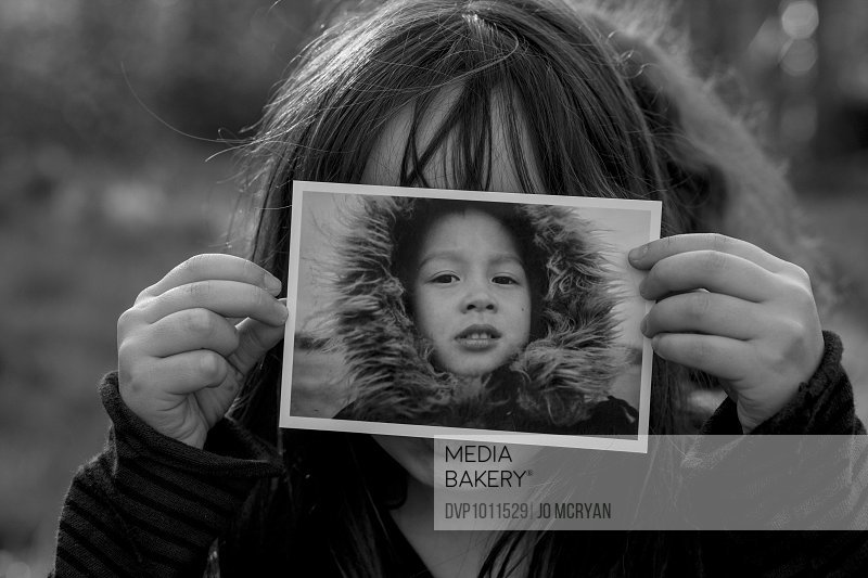 Young girl holding photo in front of her face