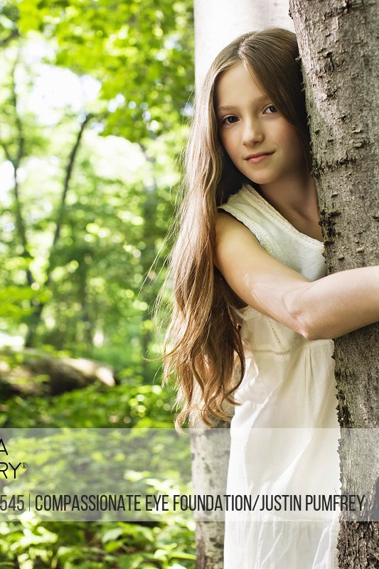 girl with long hair hugging a tree