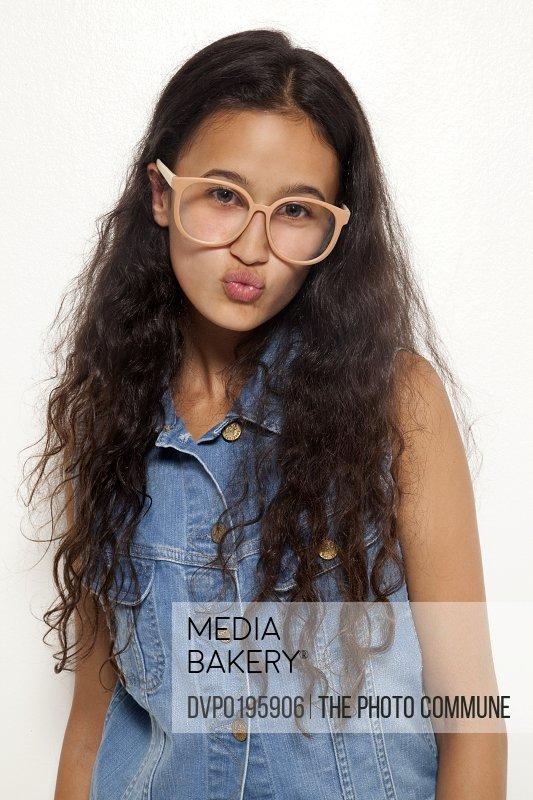 Teenage girl in studio kissing camera