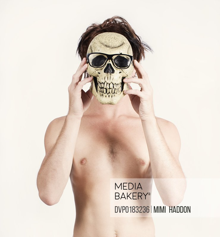 Shirtless Man Hiding Behind Skull with Glasses