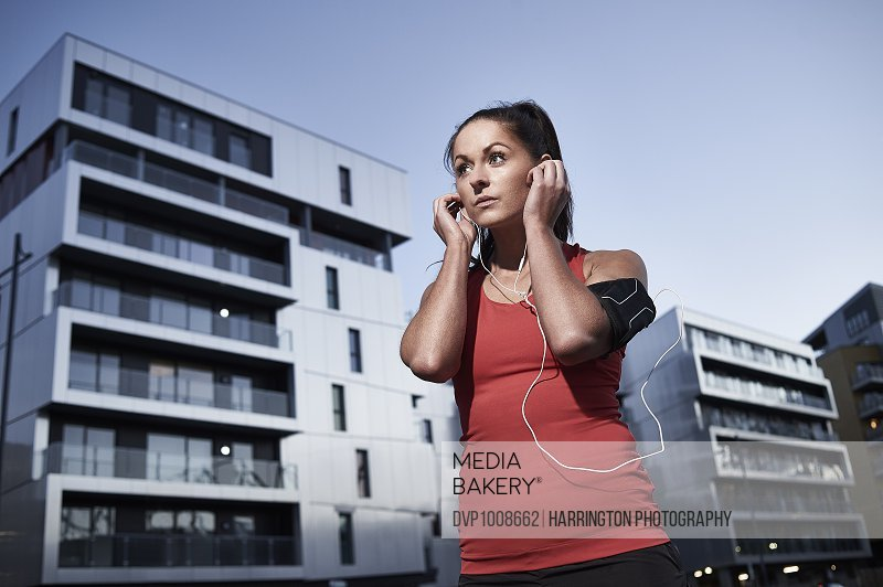 Young woman on run in urban location adjusting earphones. Wearing mobile GPS run meter.