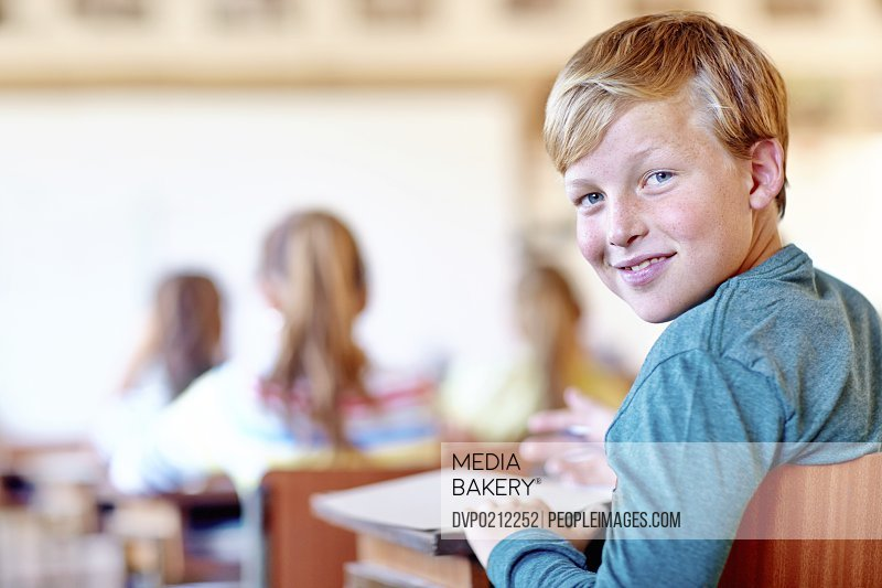 Portrait of a young male student smiling happily in class