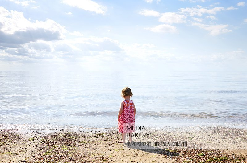 Toddler looks out to sea thoughtfully.