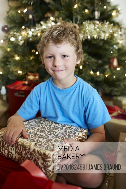 Boy with present in front of Xmas tree