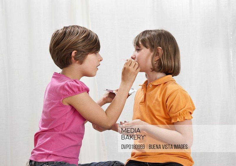 Little girls putting make up