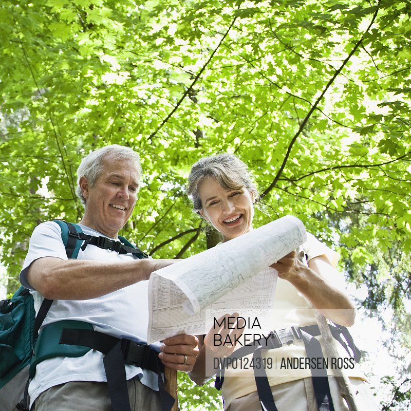 Mature couple looking at map while hiking through forest