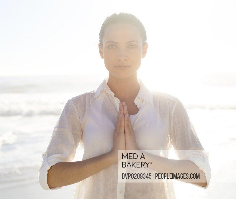 A beautiful young woman meditating outside