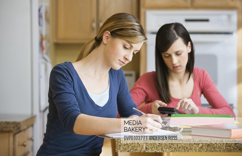 Two teenage sisters (16-18) doing homework in domestic kitchen