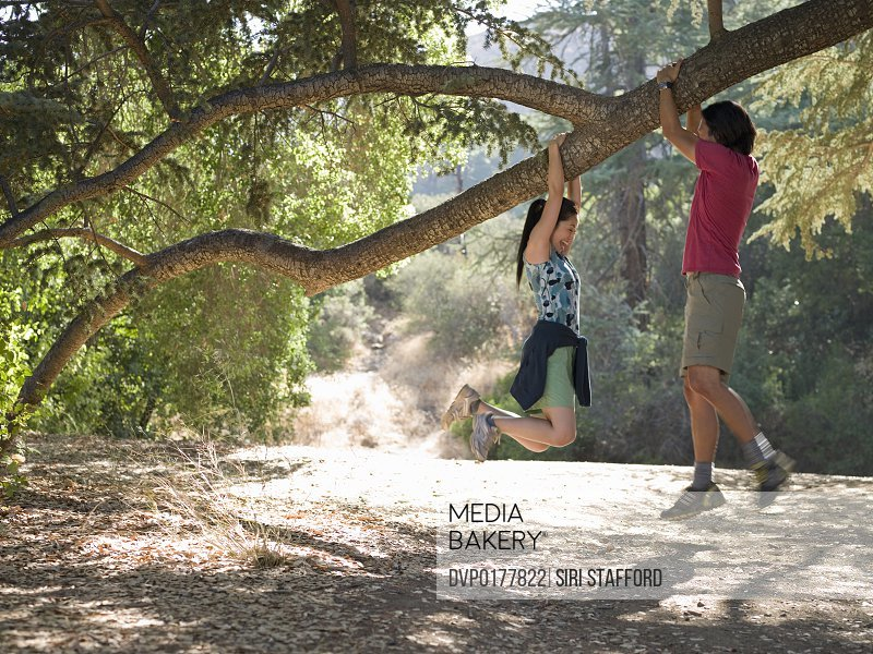 Couple dangling from tree limb