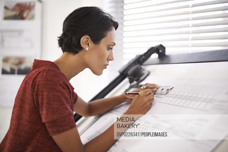 Shot of an attractive young architect working in her office
