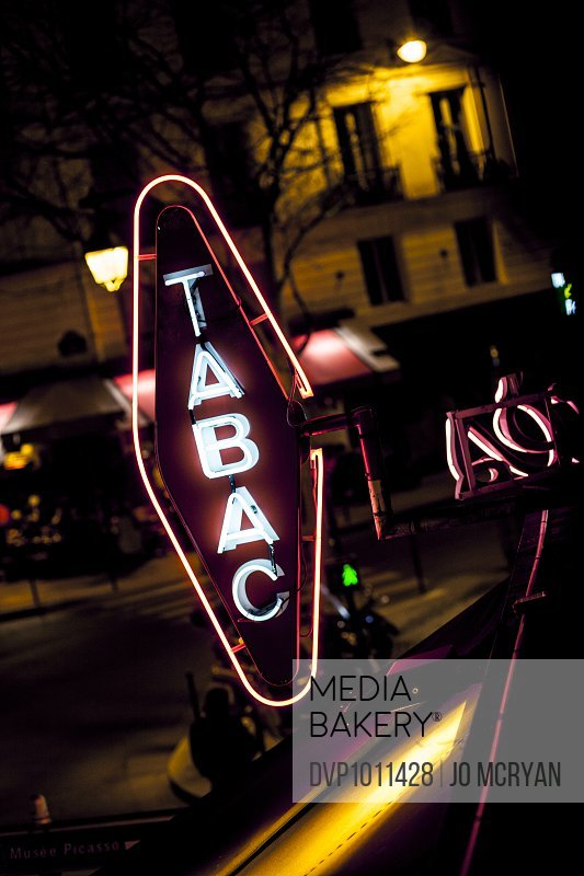 Tobacco Shop neon sign reflected with street scene