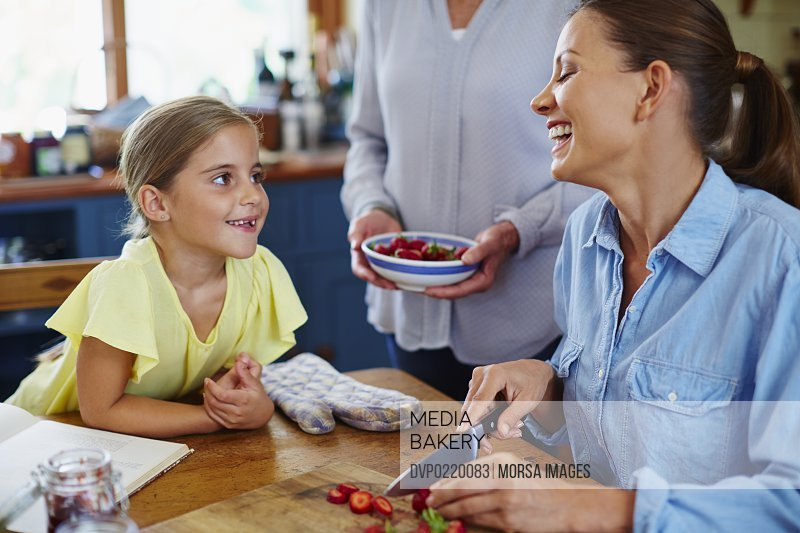 Happy three generation family chopping strawberries at table in kitchen