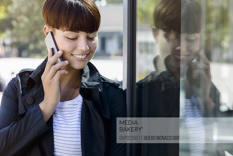 young woman chatting on smartphone in city