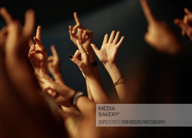 A crowd of people raising their arms to the music. This concert was created for the sole purpose of this photo shoot, featuring 300 models and 3 live bands. All people in this shoot are model released.
