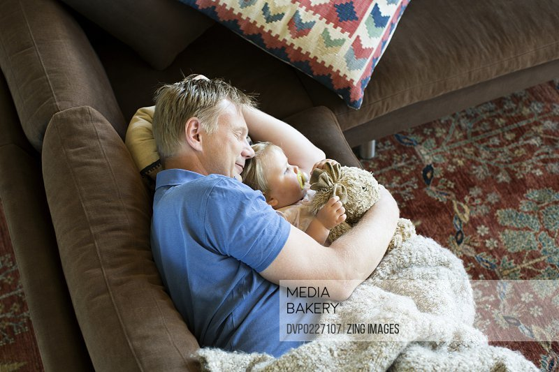 Father and female toddler 18-24 months lying on sofa