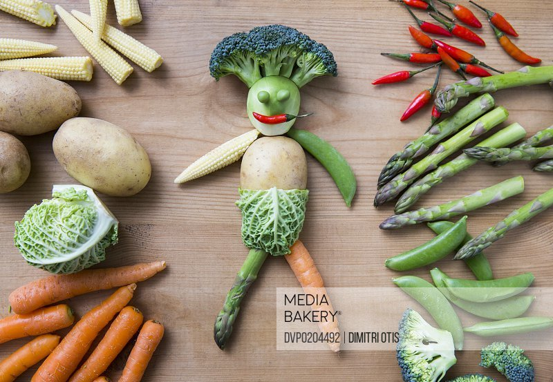 Man made of fresh vegetables on wooden surface