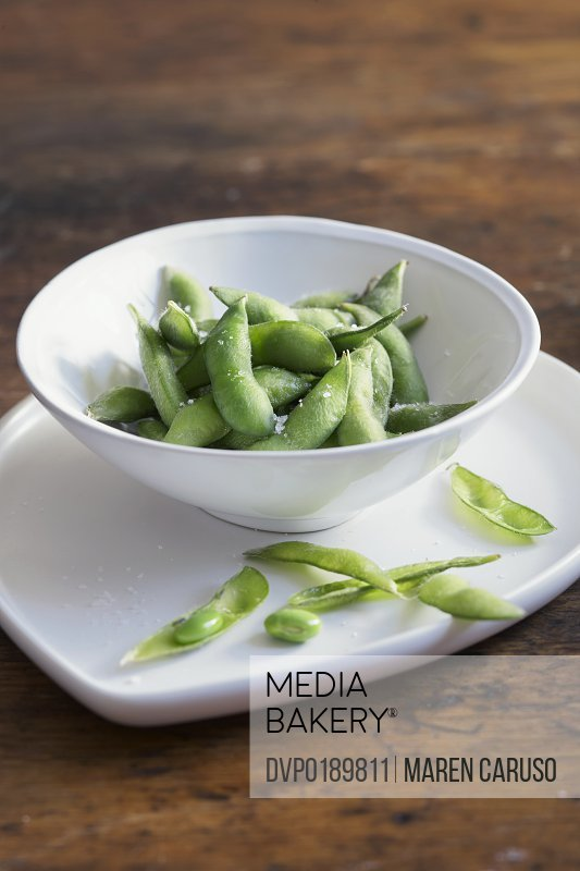 Edamame with salt in bowl on wood table
