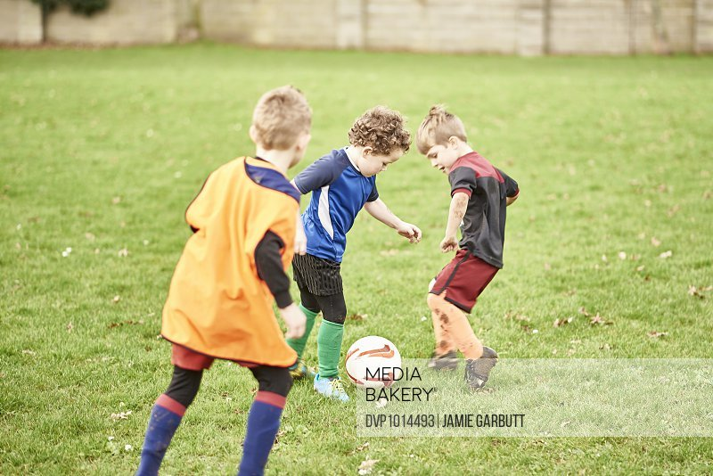 Young children playing football, at football train