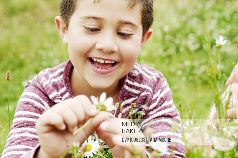 Boy in park lying in grass playing with flower