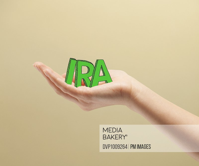 Young woman's hands holding  green illustrated block letters spelling IRA