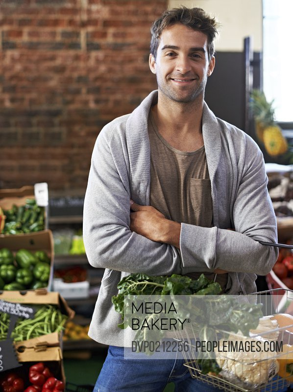Portrait of a young man in a grocery store holding a basket full of fresh produce