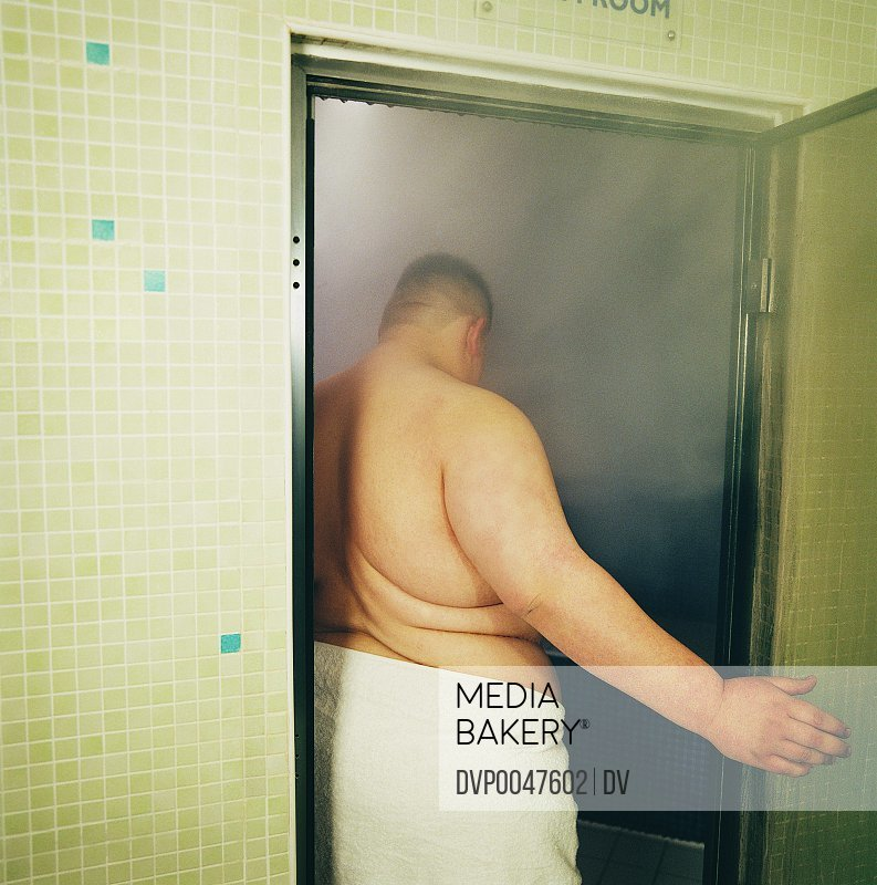 Rear View of a Fat Man Opening the Door of a Sauna