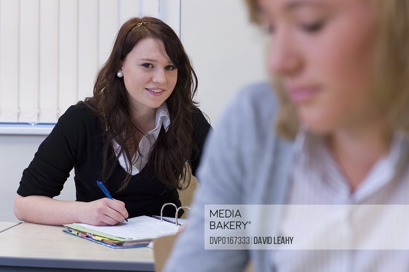 Girl in school uniform writing in school book Smiles to camera