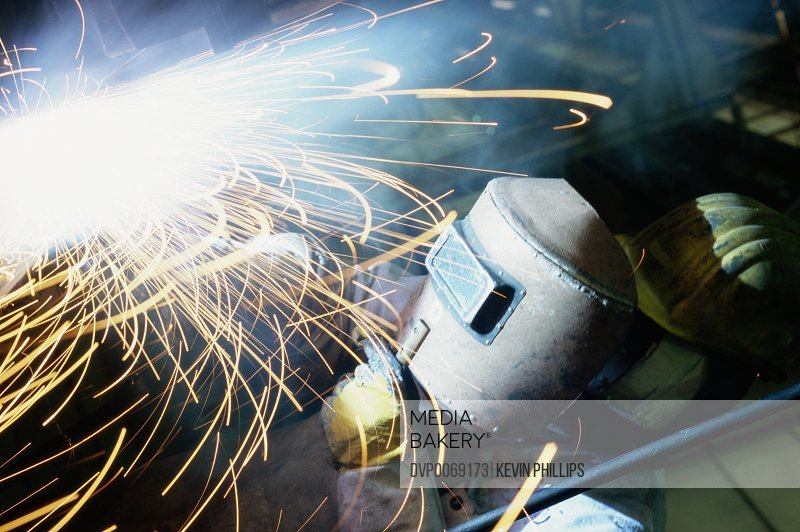 Welder holding protective mask over face (blurred motion)