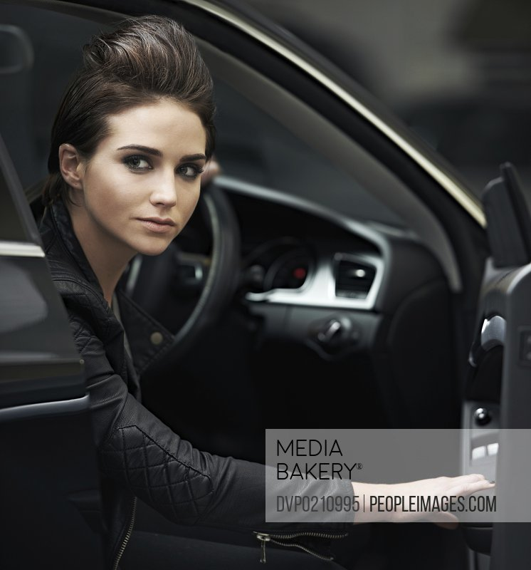 A gorgeous leather-clad woman sitting in her luxury vehicle
