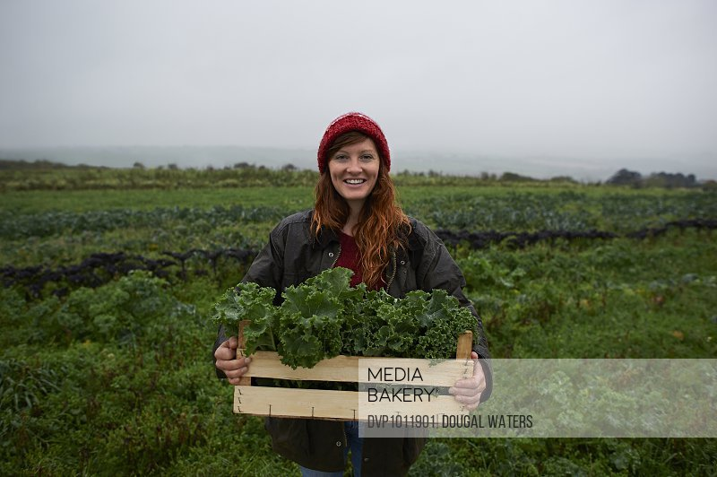 Portrait of woman holding box of kale on farm.