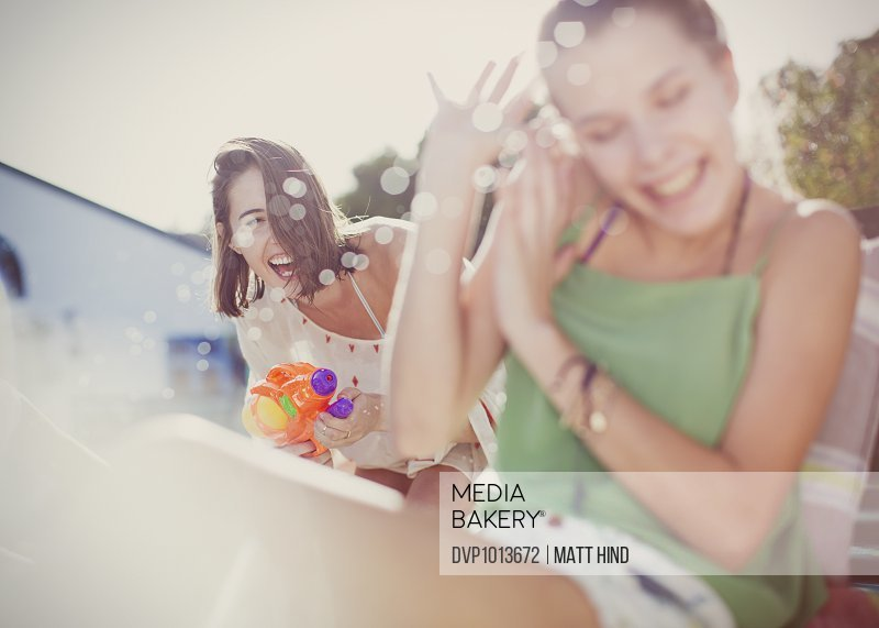 Women playing with water guns at pool party