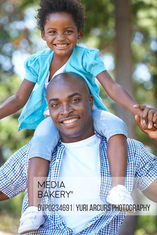 Portrait of a father carrying his daughter on his shoulders while enjoying a day outdoors