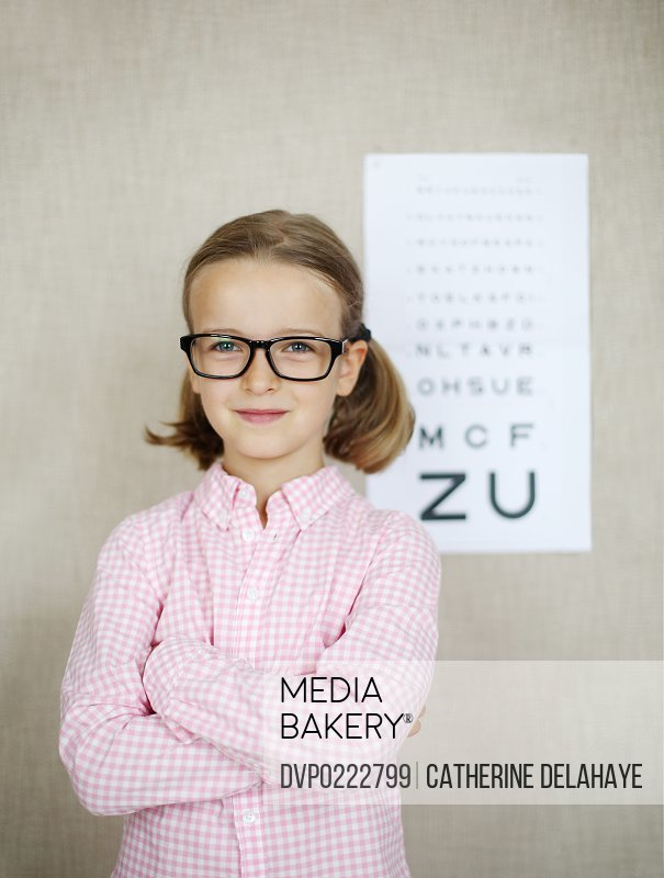 A 7 girl with glasses in front of a eye chart