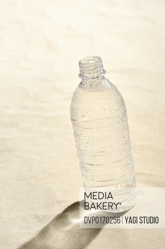 The PET bottle which contains water on the sand