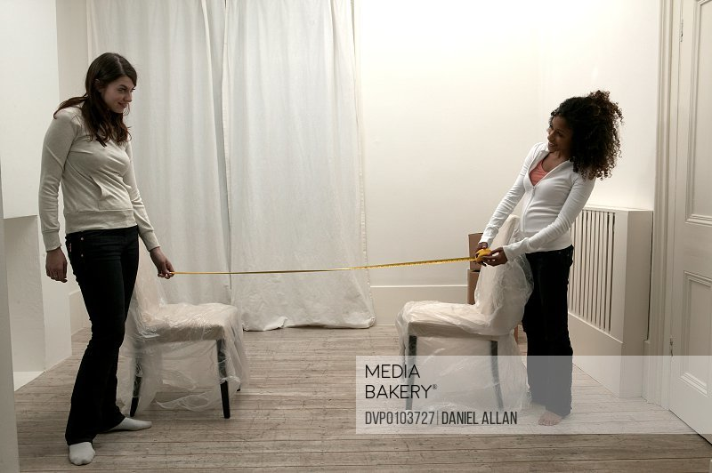 Two young women measuring distance between two plastic covered chairs
