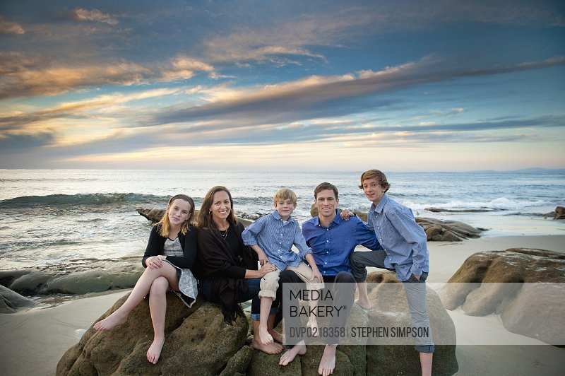family of five posing on seaside boulders