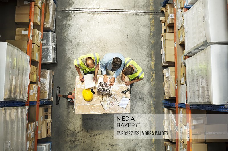 High angle view of supervisor using laptop with workers at distribution warehouse