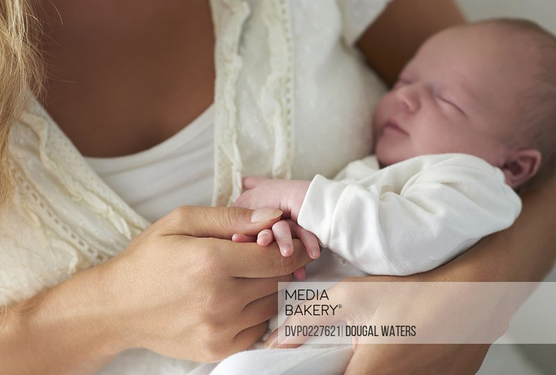 A sleeping baby holds onto his mother's finger