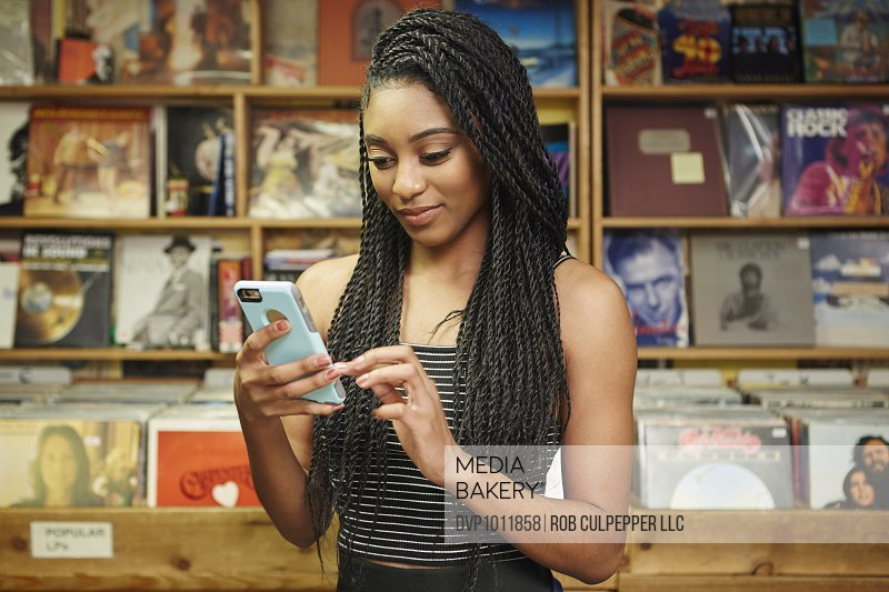Young woman texting in record shop
