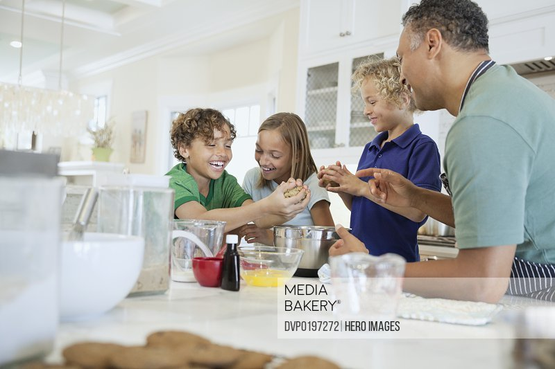 Happy father and children rolling cookie dough at kitchen counter